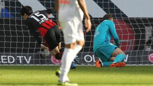 Le milieu japonais Daichi Kamada (g) ouvre le score pour Francfort lors du match de Bundesliga face au Bayern Munich, à Francfort, le 20 février 2021