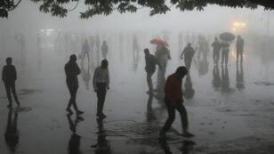 Individus pris dans la tempête, le 2 mai 2018, à Shimla, dans l'État de l'Himachal Pradesh, en Inde.