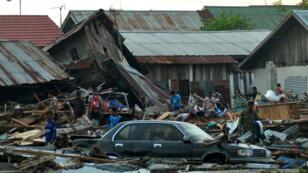 Des habitants de Palu tentent de récuperrer leurs biens après le séisme, le 29 septembre en Indonésie.