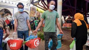 متطوعان تونسيان يرتديان كمامة يوزعان مساعدات غذائية في سوق تونس المركزية في الرابع من أيار/مايو 2020