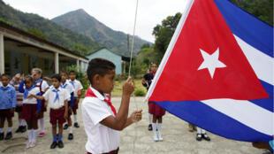 Un niño levanta la bandera de Cuba durante una ceremonia diaria que se lleva a cabo en una escuela en el pueblo de Santo Domingo, en Sierra Maestra, Cuba, el 2 de abril de 2018.