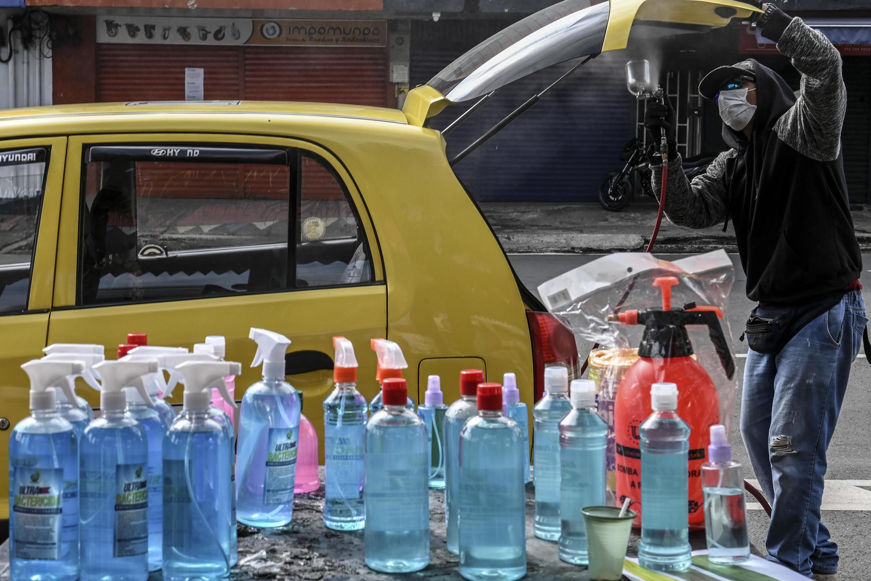 Un hombre limpia un taxi como medida preventiva ante la pandemia del coronavirus y cobra  propinas a voluntad en Medellín, Colombia, el 28 de abril de 2020