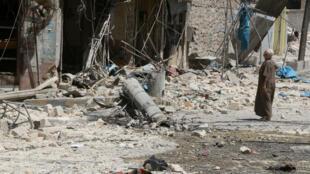 À Alep, un homme observe les décombres après un bombardement, mi-aout 2016.