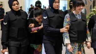 المتهمتان دوان ثي هيونغ (يمين) وستي عائشة خلال اقتيادهما إلى مسرح الجريمة في المطار كجزء من إجراءات المحاكمة 24 ت1/أكتوبر 2017