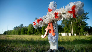 A cross with flowers and a letter A sits at the entrance to the Satilla Shores neighborhood where Ahmaud Arbery was shot and killed May 7, 2020 in Brunswick, Georgia.