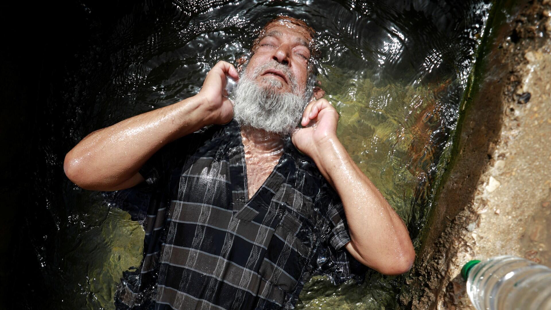 Un hombre palestino se sumerge en el agua de un manantial natural para refrescarse durante una ola de calor, en medio de las preocupaciones sobre la propagación de la enfermedad por coronavirus (COVID-19), cerca de Jericó en la Ribera Occidental ocupada por Israel el 17 de mayo de 2020.
