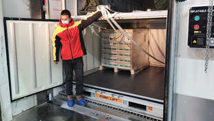Técnicos chinos preparan un envío inicial a Perú de 300.000 dosis de la vacuna de Sinopharm contra el covid-19, el 5 de febrero de 2021 en Pakín