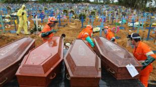 Des employés décharchent des cercueils de personnes décédées du coronavirus pour les enterrer au cimetière Nossa Senhora de Manaus, le 6 avrl 2020 au Brésil