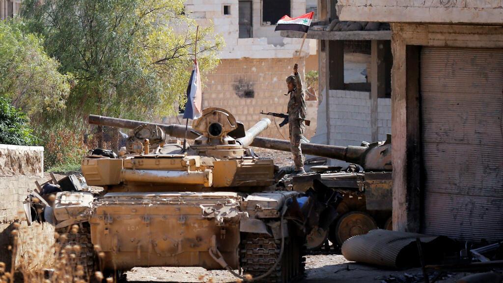 Un soldado del Ejército sirio sostiene una bandera siria mientras se encuentra en un vehículo militar en Khan Sheikhoun, Idlib, Siria, 24 de agosto de 2019.