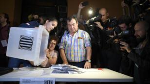 Une femme vide une urne dans un bureau de vote de Barcelone, en Catalogne, le 1er octobre 2017.
