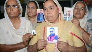 قريبات لعمال هنود خطفوا في العراق في 2014 يحملن صورا لهم خلال تجمع في أمريستار (الهند) في 28 تشرين الأول/أكتوبر 2017