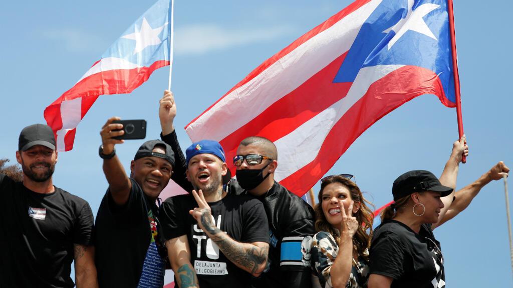 """El boxeador puertorriqueño Félix """"Tito"""" Trinidad y sus compatriotas Residente y Bad Bunny posan para una foto durante una protesta para pedir la renuncia del gobernador Ricardo Rosselló en San Juan, Puerto Rico, el 22 de julio de 2019."""