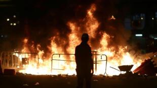 Un manifestante se encuentra cerca de un incendio provocado durante las protestas contra la prohibición de las máscaras en manifestaciones, en Hong Kong, el 4 de octubre de 2019.