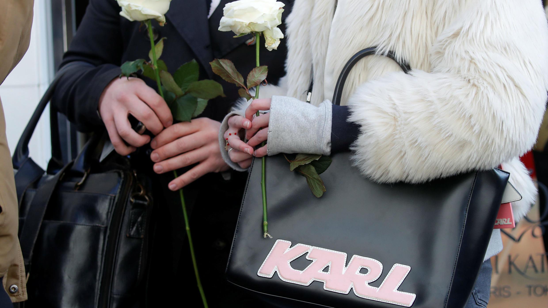 Las personas sostienen rosas blancas mientras se ubican fuera de la boutique de moda de Chanel después de las noticias de que el diseñador alemán de alta costura Karl Lagerfeld , director artístico de Chanel e ícono de la industria de la moda mundial durante más de medi