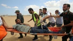 مسعفون ينقلون فلسطينيا أصيب في المواجهات على الحدود بين قطاع غزة وإسرائيل في 8 حزيران/يونيو 2018