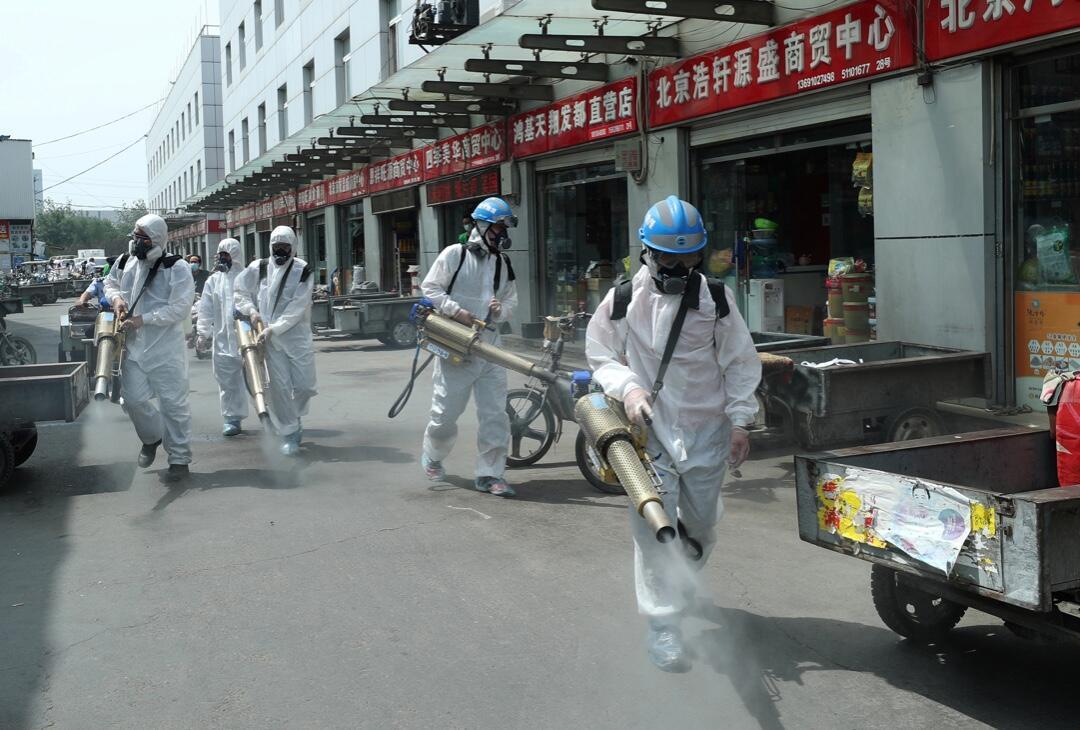 Voluntarios del equipo de rescate de Blue Sky desinfectan el mercado mayorista de Yuegezhuang, luego del registro de nuevos casos de Covid-19 en Beijing, China, el 16 de junio de 2020.