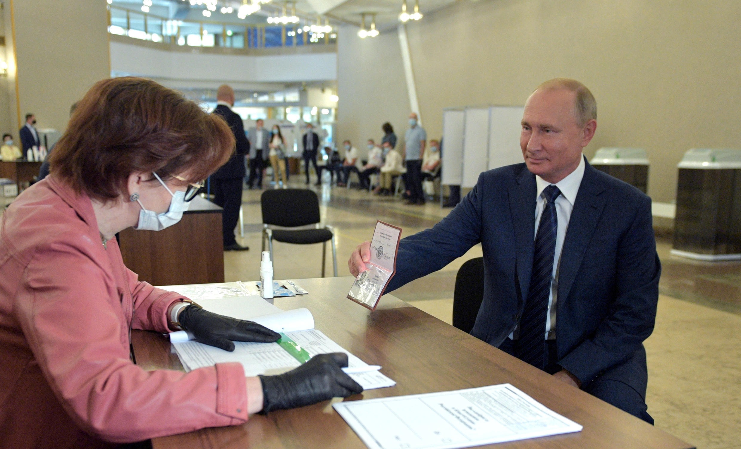 Russian President Vladimir Putin shows his passport at a polling station in Moscow on July 1, 2020.