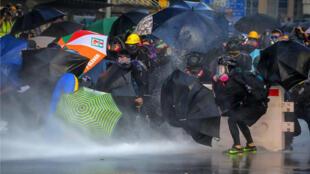 Los manifestantes usan paraguas para protegerse mientras la policía antidisturbios dispara con cañones de agua para dispersarlosen Hong Kong, el 15 de septiembre de 2019.