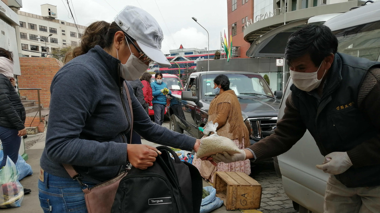 Un hombre entrega una bolsa a un comprador durante una venta de productos agrícolas en La Paz, Bolivia, el 17 de abril de 2020.