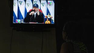 Una mujer mira una transmisión televisiva del discurso del presidente de Nicaragua, Daniel Ortega, durante el 41 aniversario de la Revolución Sandinista, el 19 de julio de 2020