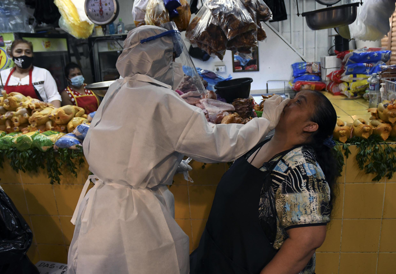 Un trabajador de la salud toma muestras para un análisis de covid-19 a una vendedora en el mercado de La Terminal en Ciudad de Guatemala, el 21 de mayo de 2020
