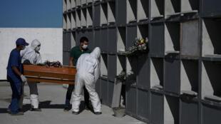 عمال بصدد وضع نعش في صندوق دفن في مقبرة بريو دي جينيرو، البرازيل، 9 أيار/مايو 2020