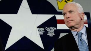 John McCain pose devant un avion de l'armée lors de campagne présidentielle 2008.