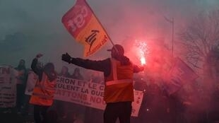 A protester burns a flare during a rally against pension reform in Paris on January 9, 2020.