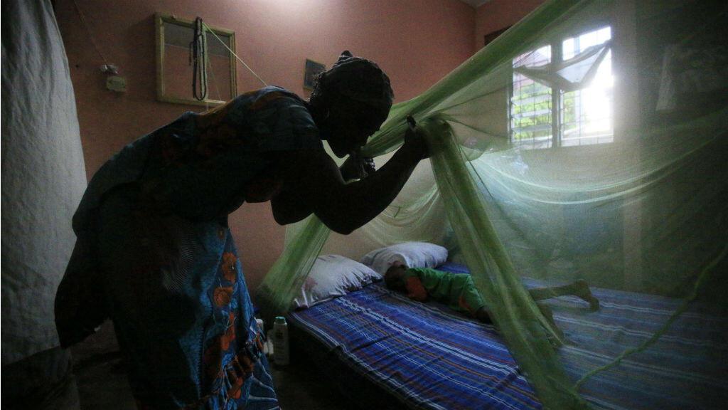 Una habitante de Abiyán, Costa de Marfil, mientras intentaba cubrir a su hijo con un toldo el 24 de abril de 2018.