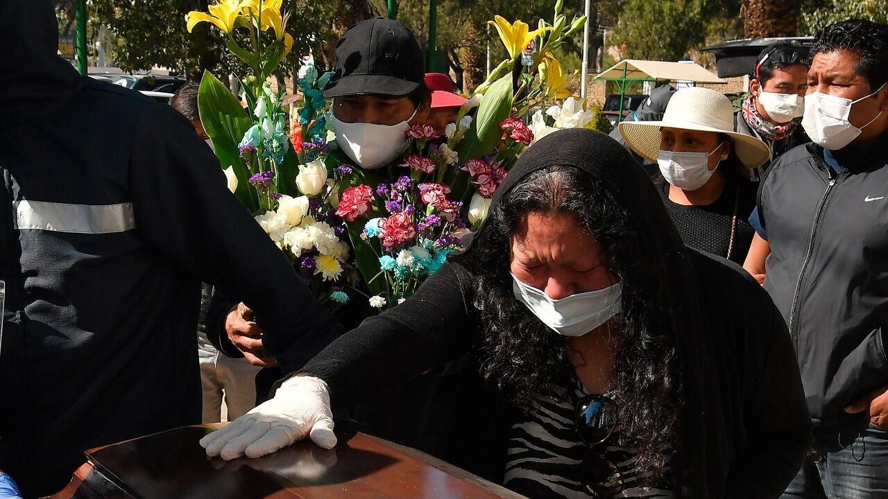 Bolivianos se despiden del féretro donde reposa su familiar a las puertas del cementerio principal de Cochabamba, Bolivia, el  1 de julio de 2020.