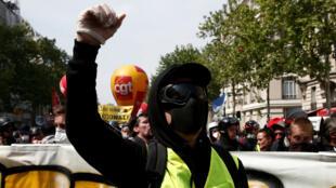 Un manifestante enmascarado que usa un chaleco amarillo asiste a la tradicional marcha del 1° de mayo. París, Francia, el 1 de mayo de 2019.