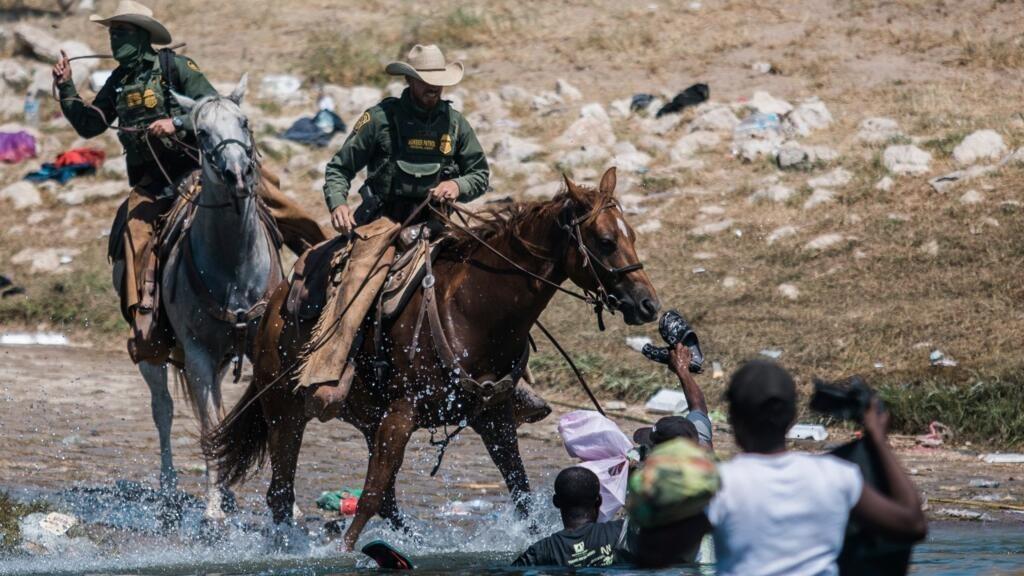 Agentes montados de la Oficina de Aduanas y Protección Fronteriza de Estados Unidos intentan contener a los migrantes mientras cruzan el Río Grande desde Ciudad Acuña, México, hacia Del Río, Texas, el domingo 19 de septiembre de 2021.