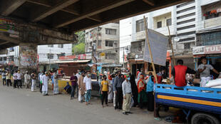 People queue to collect subsidised food in Dhaka