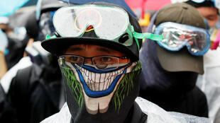 Des manifestants masqués à Hong Kong, le 6 octobre, malgré l'adoption des lois d'urgence.