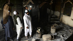 Muslim men check the interior of a partially burnt mosque on March 1, 2020 after communal riots in New Delhi
