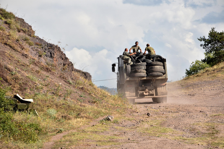Des militaires arméniens transportent des pneus usagés à l'arrière d'un camion pour fortifier leurs positions à la frontière arméno-azerbaïdjanaise près du village de Movses, le 15 juillet 2020.