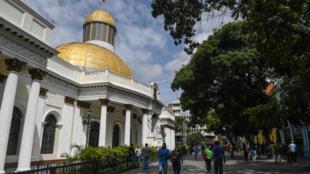 Varias personas con mascarilla pasan por delante de la Asamblea Nacional de Caracas el 14 de julio de 2020
