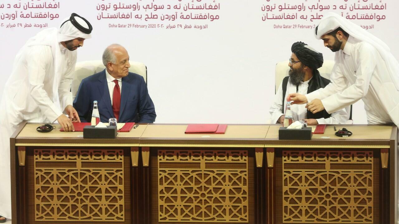 US peace envoy Zalmay Khalilzad, left, and Mullah Abdul Ghani Baradar, the top political leader of the Taliban group, sign a peace agreement between Taliban and US officials in Doha, Qatar, on February 29, 2020.
