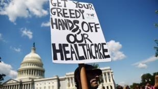 Un manifestante sostiene un cartel durante una manifestación de senadores demócratas para oponerse a la derogación de la Ley del Cuidado de Salud a Bajo Precio y su reemplazo en Capitol Hill, Washington, EE. UU., el 21 de junio de 2017.