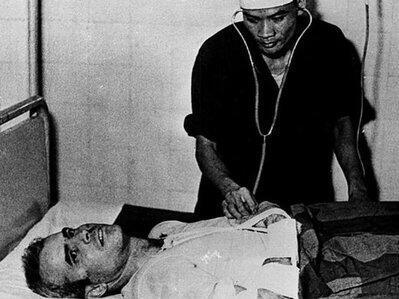 John McCain soigné par un soldat vietnamien en 1967, après que son avion a été abattu par des soldats nord-vietnamiens lors de la Guerre du Vietnam.