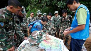 Los equipos de emergencia tailandeses examinan un mapa antes de proceder al rescate de doce niños y un adulto atrapados al interior de una cueva en Tailandia. 7 de julio de 2018.