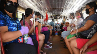 Passengers travel on a jeepney with seat dividers to ensure social distancing in Manila. Residents of Navotas, one of the poorest areas of the capital, will go back into lockdown following a spike in new coronavirus cases
