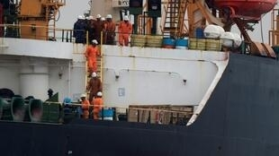 """(FILES) In this file photo taken July 06, 2019 Crew members walk down a ladder on board supertanker Grace 1 off the coast of Gibraltar on July 6, 2019. Gibraltar's Chief Minister Fabian Picardo has said he had a """"constructive and positive"""" meeting with Iranian officials in London aimed at defusing tensions around an oil tanker carrying Iranian oil being held in the British territory's waters"""