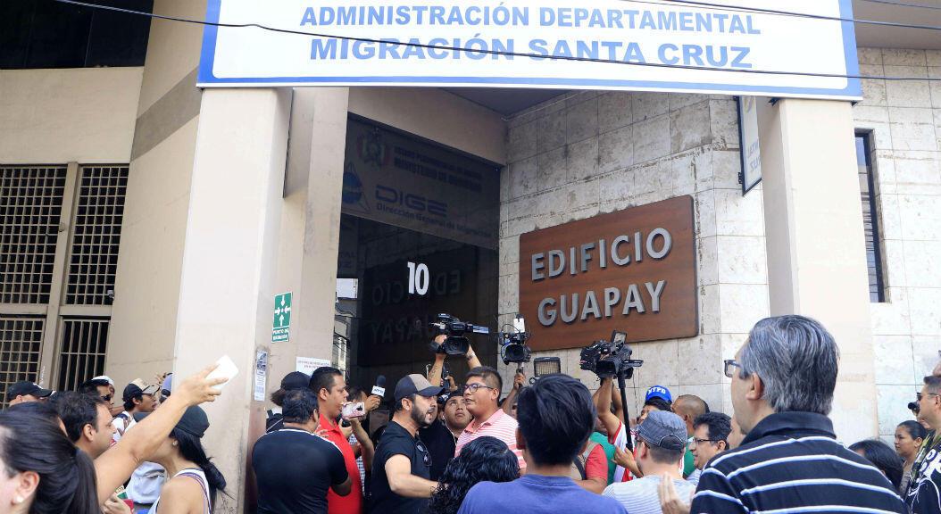 Un grupo de gente frente a una entidad estatal cerrada por protestas, en Santa Cruz, Bolivia, el 5 de noviembre de 2019. Los comités cívicos han llamado a bloquear instituciones del Estado para forzar la renuncia del presidente del país, Evo Morales, a quien acusan de f