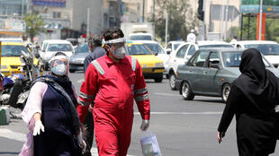 إيرانيون يضعون كمامات واقية يعبرون شارعا في طهران في 9 أيار/مايو 2020 وسط تفشي فيروس كورونا المستجد