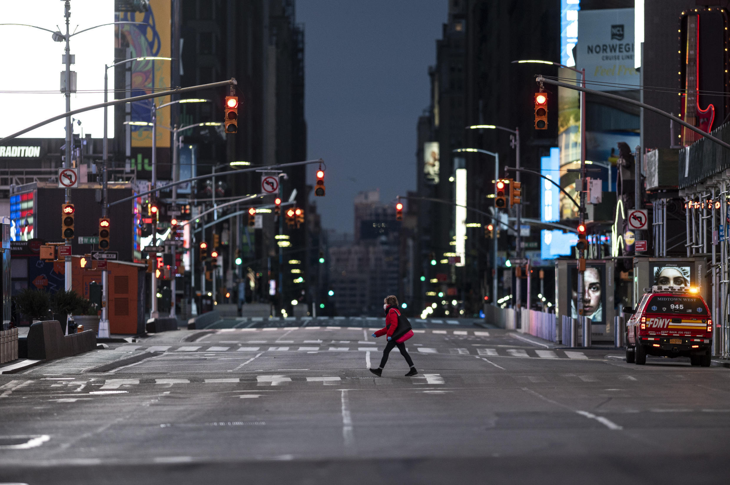 A woman walks through an almost-deserted Times Square in the early morning hours on April 23, 2020, in New York City, USA.