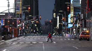 A woman walks through an almost-deserted Times Square in the early morning hours on April 23, 2020 in New York City