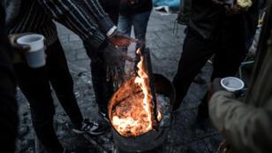 Solicitantes de asilo del este de África, principalmente de Sudán, se calientan alrededor de un brasero mientras comen alimentos ofrecidos por voluntarios de la asociación 'Solidarite migrants Wilson', en Saint-Denis, en las afueras de París, donde viven en un campamento de tiendas improvisado. 10 de enero de 2019.