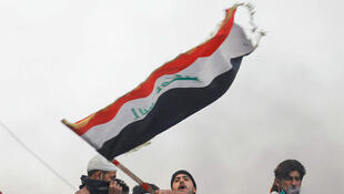 A demonstrator carries the Iraqi flag during ongoing anti-government protests in Baghdad, Iraq, November 30, 2019.