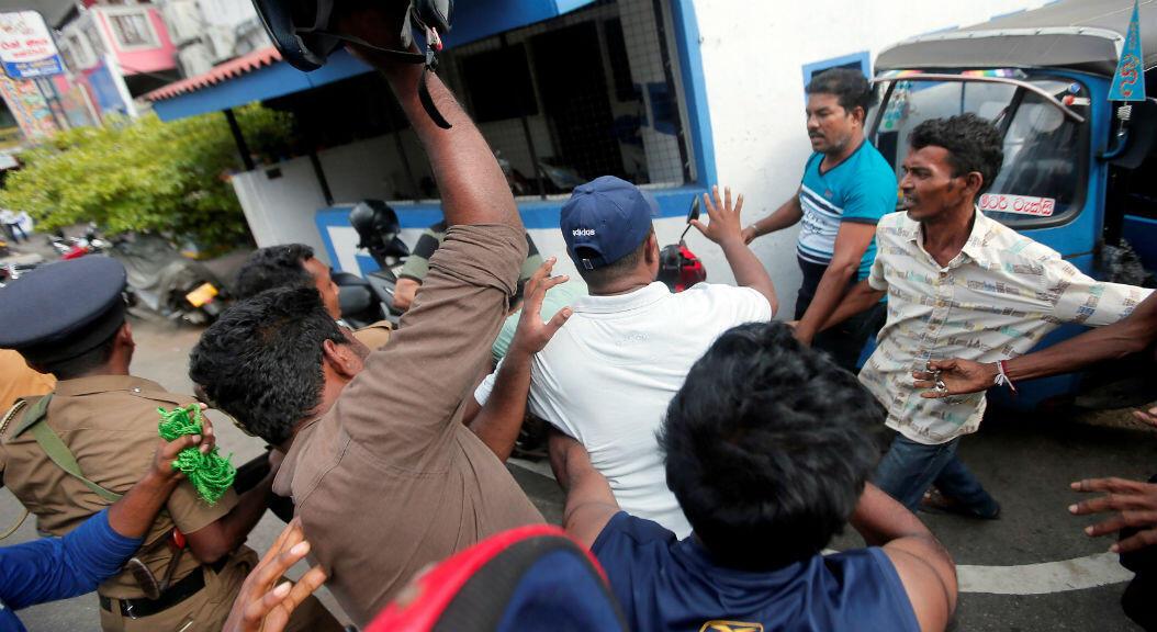 Un grupo de personas que vive cerca de una iglesia, que fue atacada el 21 de abril, intentan golpear a una persona detenida por la policía, el 22 de abril de 2019, en Colombo, Sri Lanka.